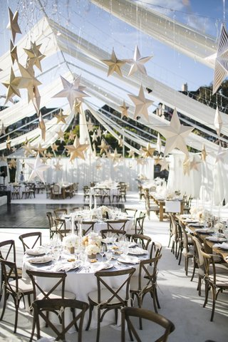 gold-paper-stars-suspended-from-ceiling-over-tables