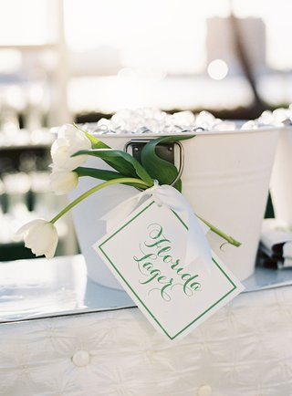 white-and-green-florida-lager-beer-sign-at-wedding-on-white-ice-bucket-and-white-tulip-flowers