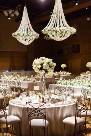 gold-chameleon-chairs-at-wedding-reception-with-inverted-glass-vase-with-white-roses-and-hydrangeas