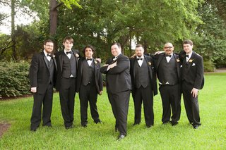 groom-with-six-groomsmen-in-tuxedos-on-grass-lawn