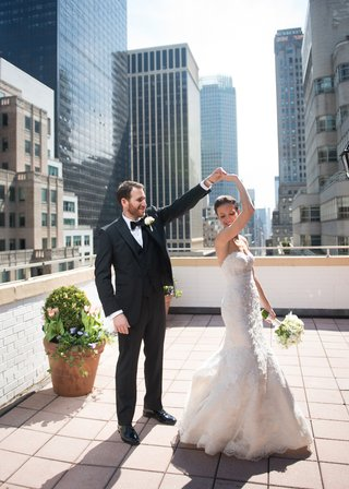 groom-in-a-black-tuxedo-twirling-his-bride-clad-in-a-white-wedding-gown-on-a-rooftop-in-nyc
