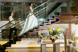 bride-in-inbal-dror-ball-gown-groom-in-white-tuxedo-jacket-walking-up-stairs