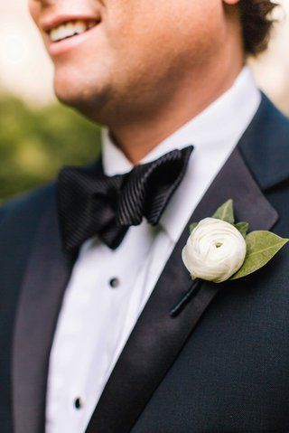 close-up-of-grooms-tuxedo-and-white-ranunculus-boutonniere-with-green-leaves