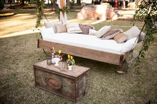 outdoor-wedding-rustic-antique-coffee-table-day-bed-suspended-from-tree-with-pillows-for-lounge-area