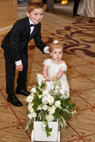 ring-bearer-in-small-tuxedo-with-flower-girl-pushing-flower-cart-at-hotel-ritz-carlton