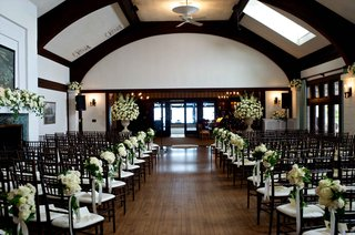 wedding-ceremony-in-country-club-ivory-rose-greenery-bouquets-along-aisle-mantle-urns