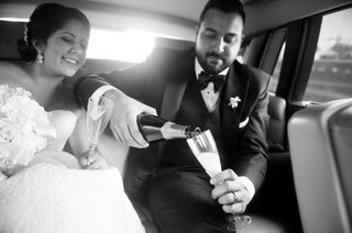 black-and-white-photo-of-bride-and-groom-pouring-champagne-into-flutes-in-back-of-rolls-royce
