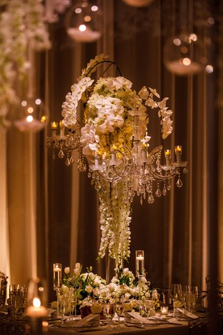 wedding-reception-tall-centerpiece-chandelier-white-orchid-and-roses-tulip-flowers-at-base-candles