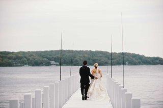 bride-in-a-strapless-vera-wang-dress-updo-veil-walks-with-groom-in-black-tuxedo-on-lake-geneva