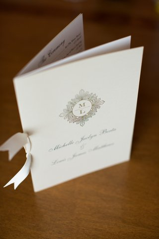 white-bow-tied-to-wedding-program-with-monogram