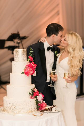 bride-and-groom-kiss-with-champagne-at-wedding-cake-white-gold-splatter-design-bright-pink-flowers