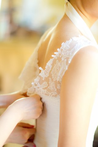 bride-gets-help-putting-on-her-sleeveless-vera-wang-dress-with-lace-neckline