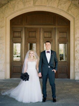 fall-themed-wedding-white-wedding-dress-dark-black-purple-bouquet-groom-in-dark-suit-and-bow-tie