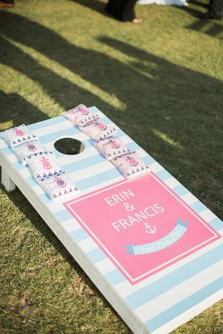 baby-blue-and-white-striped-corn-hole-with-pink-square-and-names-with-anchor-and-bean-bags