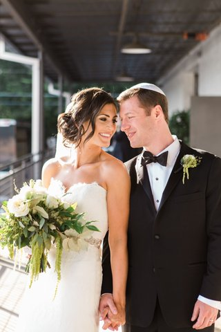 bride-and-groom-smile-and-hold-hands-with-white-and-green-bouquet-and-yamulke