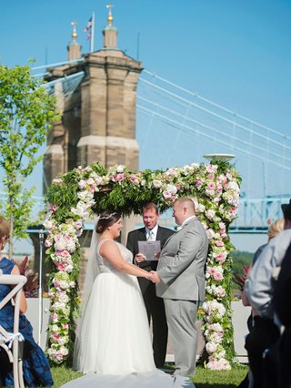 wedding-ceremony-with-bridge-in-background-flower-greenery-arch-bride-in-sleeveless-gown-grey-suit