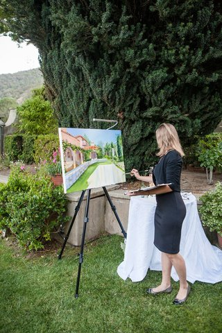 an-artist-doing-a-painting-of-the-couples-outdoor-reception-space-at-estate-in-northern-california