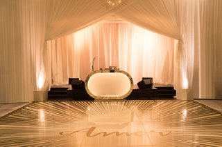 dj-booth-with-silver-gold-metallic-border-and-custom-dance-floor-wedding-amor-with-sunburst-motif