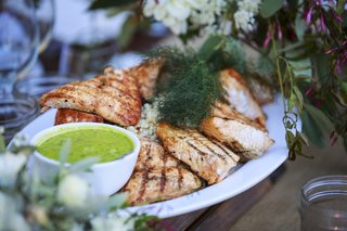 rustic-outdoor-wedding-reception-table-with-platter-of-grilled-salmon-risotto-green-sauce-dill
