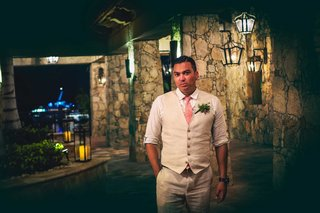 a-groom-in-a-dark-hallway-poses-in-a-tan-suit-with-pink-tie-and-green-boutonniere