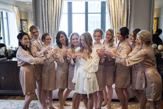 bride-in-white-robe-lace-trim-with-bridesmaids-champagne-robes-champagne-flutes-cheers-toast