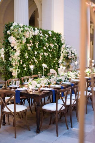 wedding-reception-greenery-wall-white-pink-flowers-navy-napkins-wood-vineyard-chairs-and-table