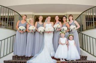 bridesmaids-in-v-neck-silver-gowns-with-bouquets-white-flowers-dusty-miller-flower-girls-crowns