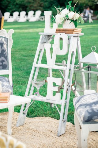 small-white-ladder-with-letters-that-spell-out-love-large-lantern-and-white-blue-settees-and-rug