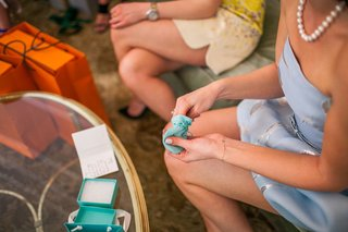 bride-to-be-at-bridal-shower-opening-tiffany-co-gift-from-blue-box