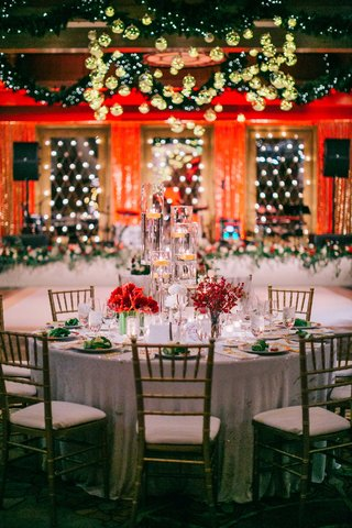 white-linen-gold-chairs-red-flowers-tall-floating-candles-gold-ornaments-green-garland-dance-floor