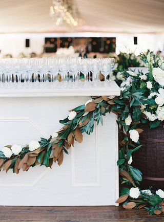 white-bar-with-wine-glasses-on-top-decorated-with-magnolia-leaf-garland-and-white-flower-wine-barrel