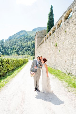 bride-in-sleeveless-wedding-dress-groom-in-grey-suit-and-fedora-italy-wedding-venue-destination