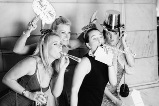 black-and-white-photo-of-wedding-guests-in-photo-booth-with-noise-makers-hats-and-signage