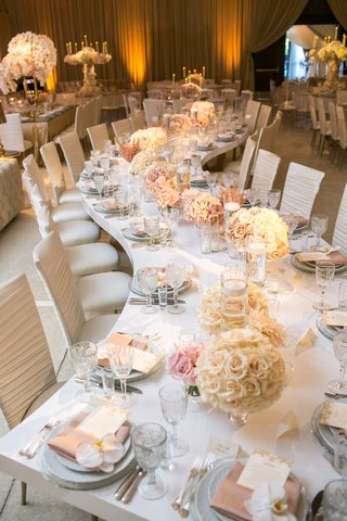 a-long-serpentine-table-with-round-white-rose-arrangements-along-the-center