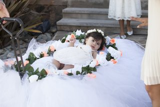 young-flower-girl-pulled-down-aisle-in-wagon-decorated-with-tulle-pink-rose-white-rose-greenery