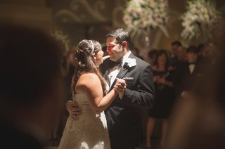 bride-in-a-strapless-watters-lace-dress-with-off-white-sash-dances-with-groom-in-black-tuxedo