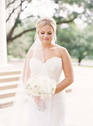 bride in strapless sweetheart neckline wedding dress holding white bouquet blond hair pulled back