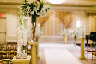 wedding-ceremony-with-submerged-white-orchid-stems-and-floating-candle-on-golden-pedestal