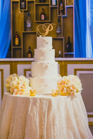 four-tier-white-wedding-cake-with-floral-appliques-and-a-gold-p-cake-topper