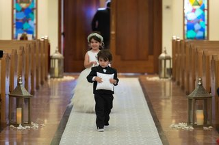 ring-bearer-in-sneakers-and-tuxedo-holding-white-pillow-flower-girl-in-tulle-ball-gown-flower-crown