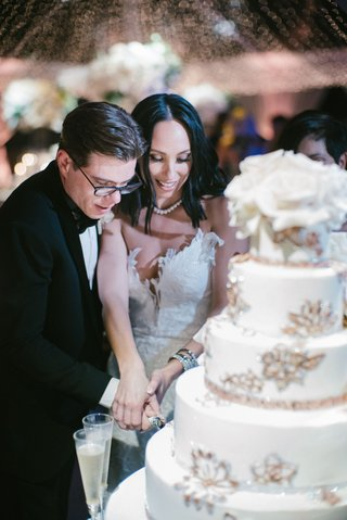 cheryl-burke-and-matthew-lawrence-cutting-into-wedding-cake-bride-in-second-dress-white-gold-cake