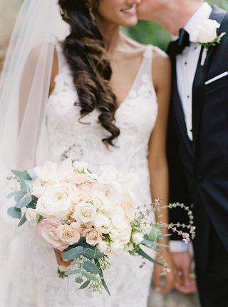 groom-kissing-bride-on-cheek-liancarlo-spanish-lace-wedding-dress-white-pink-rose-bouquet-greenery