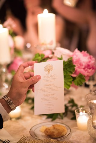 guest-holds-printed-dinner-menu-for-wedding-reception-with-gold-print-and-tree-design