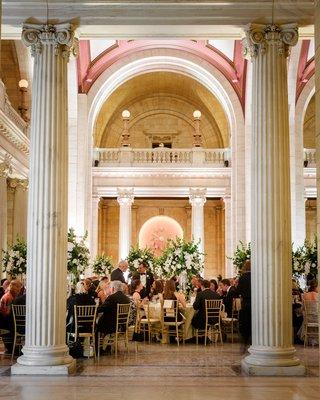 wedding-reception-dinner-hall-tall-columns-gold-chairs-white-green-centerpiece-designs-decor