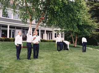 groomsmen-in-tuxedos-playing-croquet-and-lawn-games-at-family-lake-house-in-new-hampshire