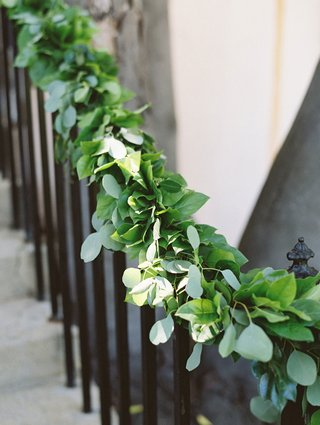 outdoor-ceremony-space-with-a-winding-staircase-railing-lined-with-green-foliage