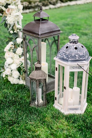 wedding-ceremony-outdoor-grass-lawn-antique-style-candle-lantern-decor-under-ceremony-arch-flowers