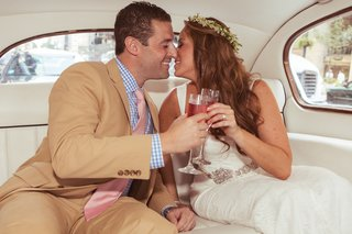 boho-bride-and-groom-toast-champagne-in-classic-car
