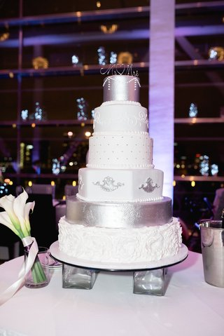 wedding-cake-on-legs-with-white-silver-and-cream-decorations-different-designs-on-each-layer