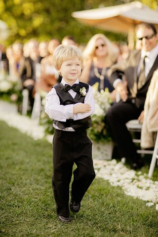 cute-blond-ring-bearer-on-grass-aisle-white-flower-petals-vest-boutonniere-and-bow-tie